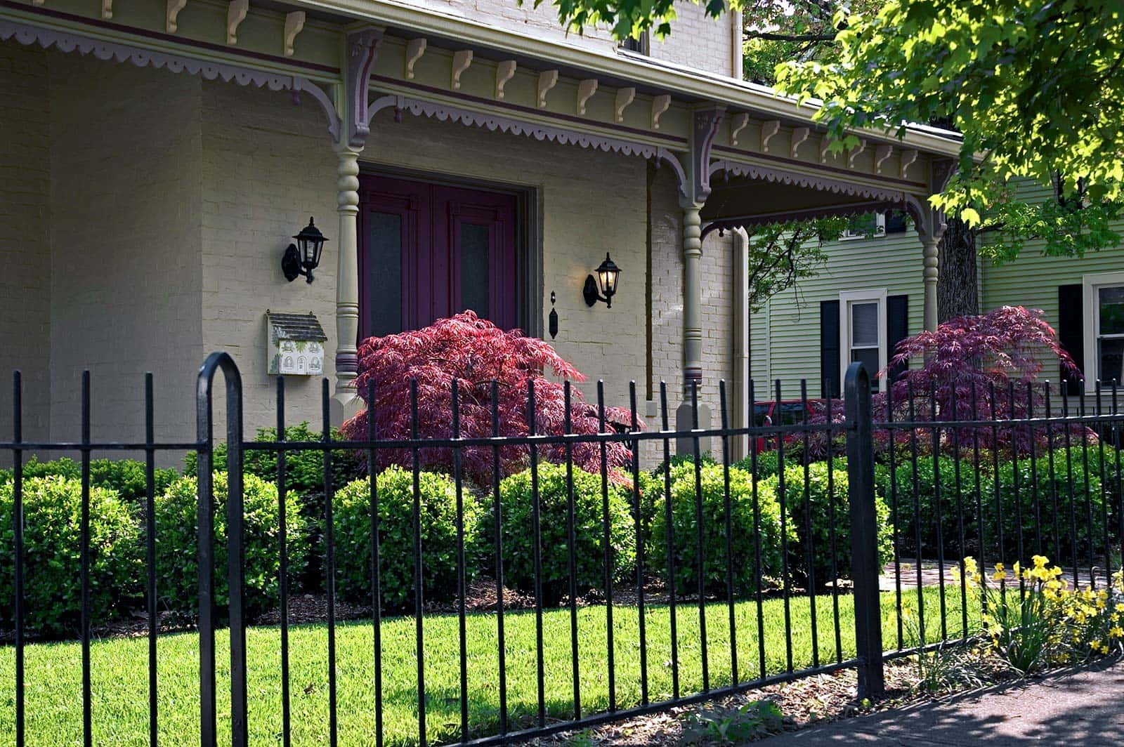 Iron ornamental fence that is defining an area while giving great curb appeal to the home and yard