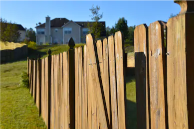 damaged-fence-needed-fence-repair.-Nails-and-screws-coming-loose-from-wood-slats-or-planks-and-discoloring