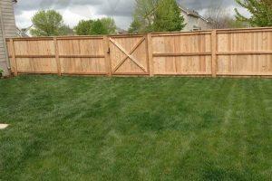 wood-spokane-privacy-fence-around-backyard-with-green-grass